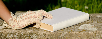 mano-gloved-del-merletto-sul-libro-bianco-24716013
